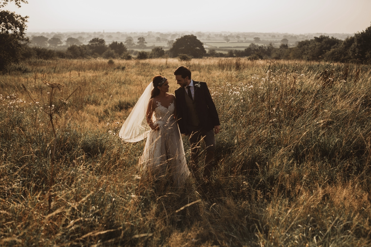 Couple pose for photos in wild meadow