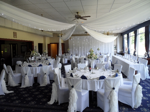 Wedding reception layout at Haydock Park Golf Club with ceiling drapes and fairylights