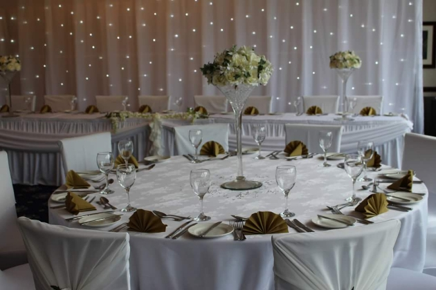 Wedding reception layout at Haydock Park Golf Club with flower-filled martini glass centrepieces