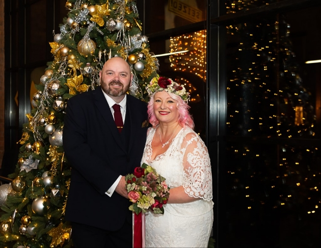 karen and david in front of christmas tree, dressed in their wedding finery