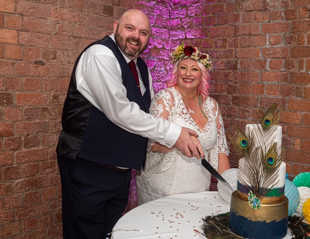 newlyweds karen and david cutting their wedding cake