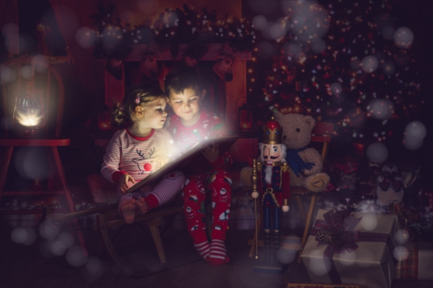 Little boy and girl reading a christmas book in front of the christmas tree