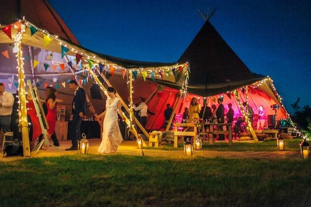 Colourful tipi wedding celebrations at nighttime