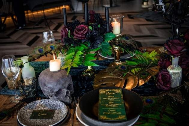 alternative wedding table scape complete with black candles and plates and skull candle holder