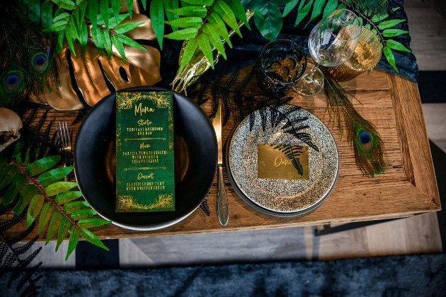 wedding table scape with black plate and emerald green and gold menu design