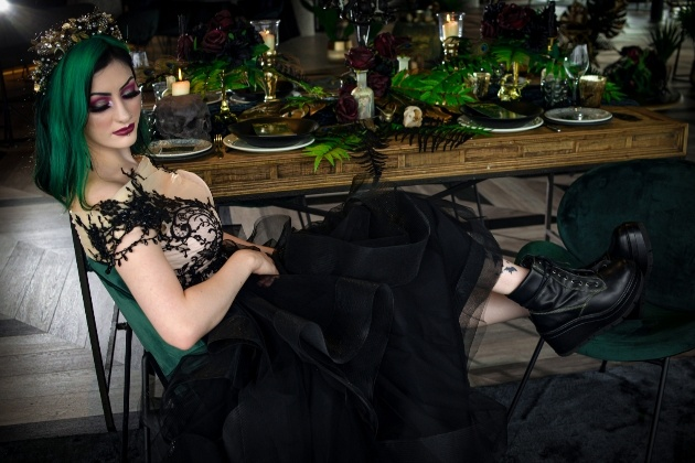 Bride dressed in black sitting at wedding reception table