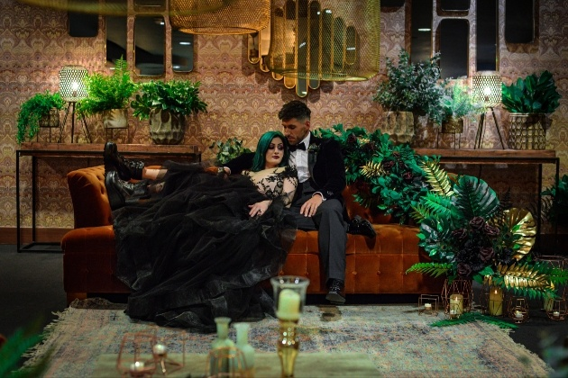 bride and groom snuggle on sofa surrounded by gold and green foliage