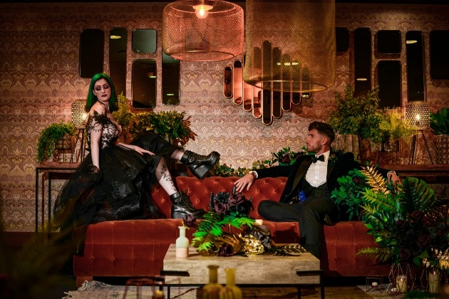 bride and groom on sofa at their venue, bride shows off her black platform boots