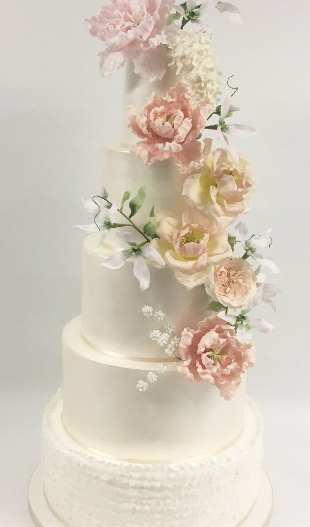 4tier wedding cake with pastel flowers and white icing