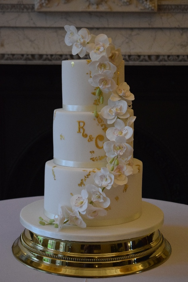 White wedding cake with couple's initials in gold and orchid sugar flowers