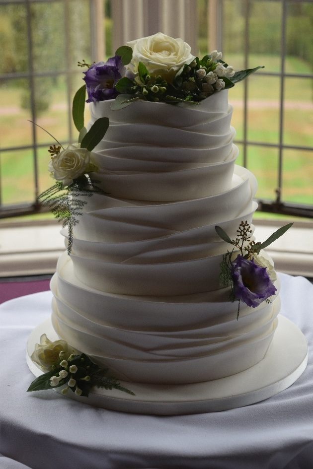 Ruffled icing wedding cake with white and blue flowers