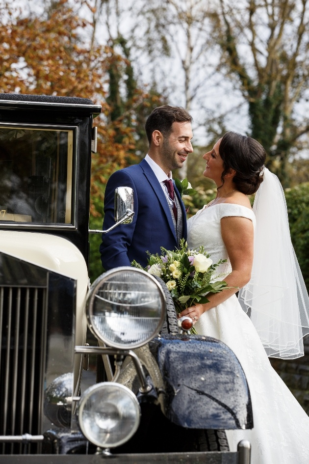 Couple pose with wedding car