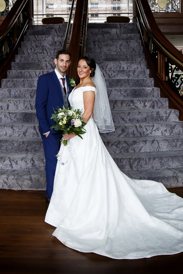 Couple pose in front of staircase