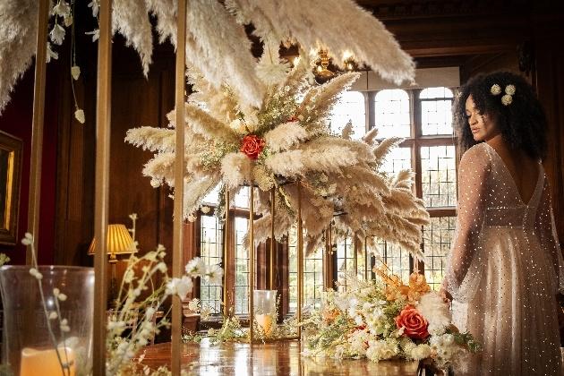 Bride admiring wedding table set up with stunning pampas grass arrangements