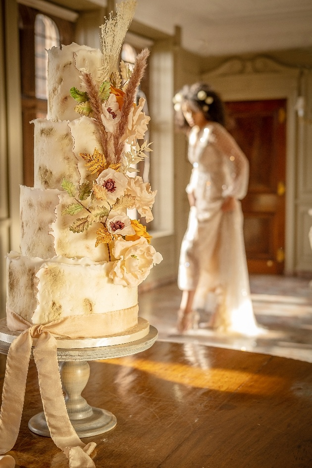 textured wedding cake decorated in sugar flowers and pampas grass