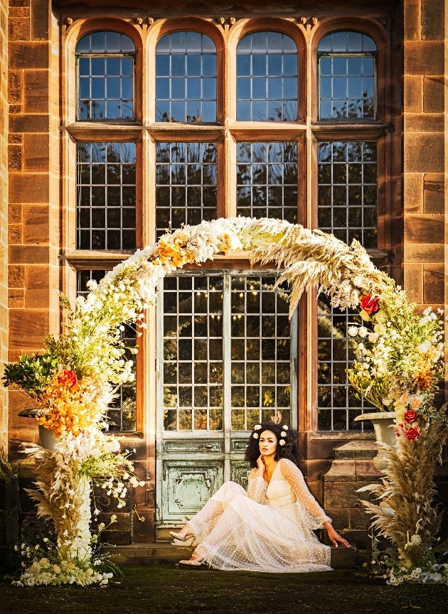 bride sitting on steps at thornton manor beneath a floral arch