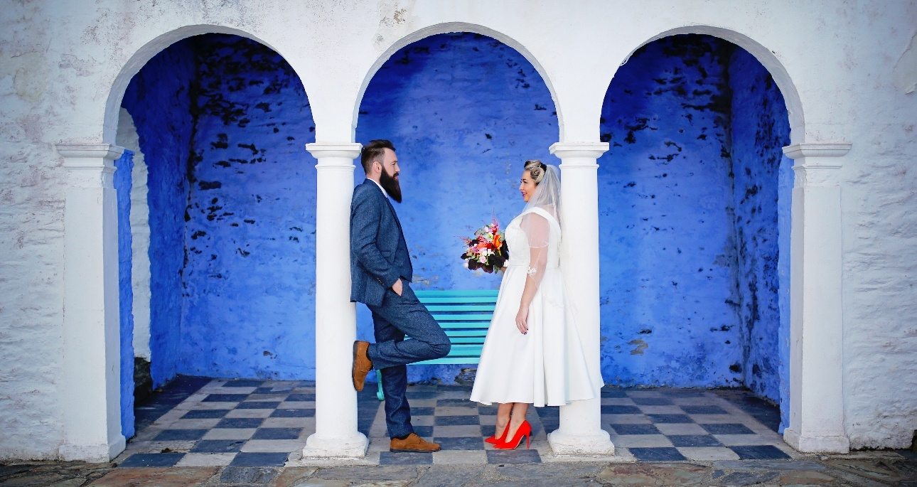 Couple standing beneath arches painted in white and blue in Portmerion