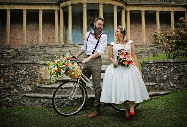 bride and groom in portmerion leaning on a bicycle