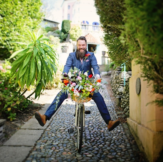 groom on a bicycle free wheeling down a cobbled street in portmerion
