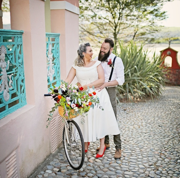 bride and groom smile at one another while proping up a bicyle