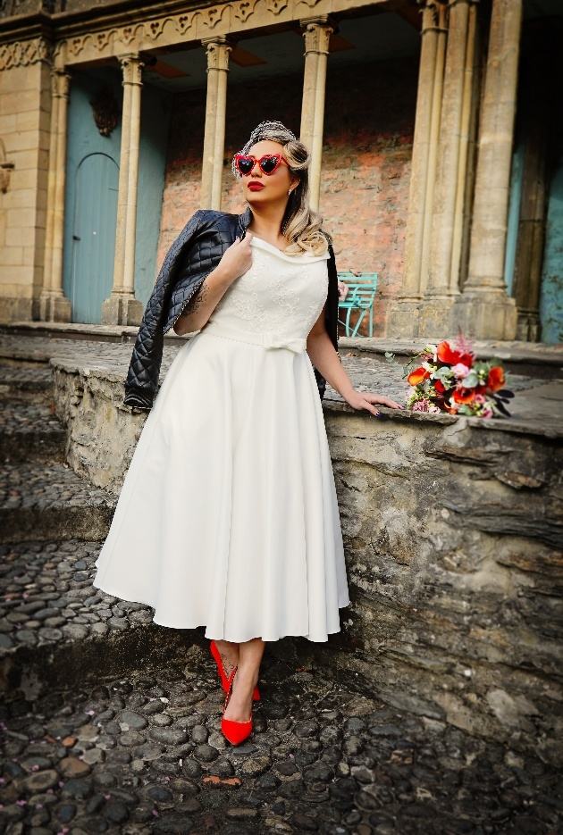 bride wearing tea-length dress, heart-shaped sunglasses, leather jacket and red shoes