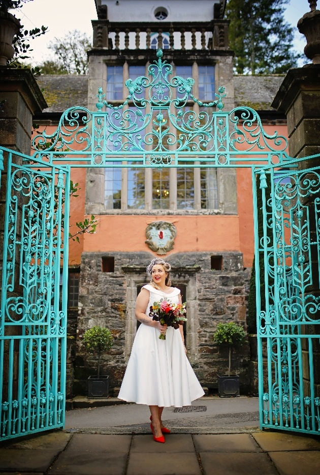 Bride in front of teal green gates in portmerion