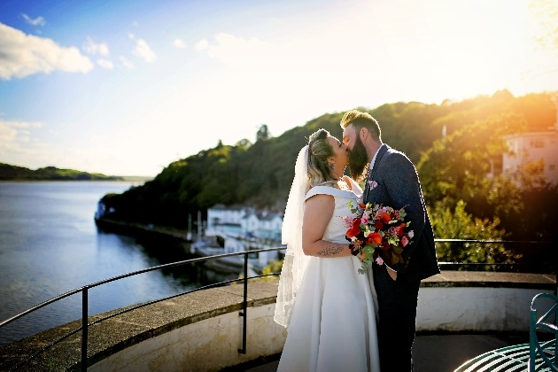 bride and groom kiss in front of the north wales coastline