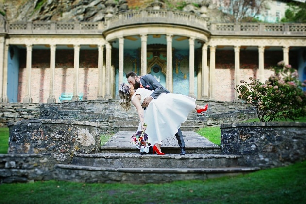 bride and groom dip and kiss on steps of portmerion gardens