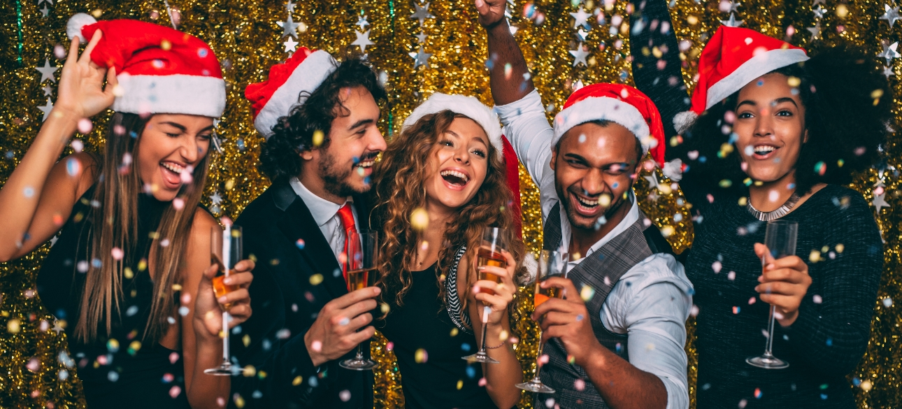 Five people celebrating at a christmas party with champagne and wearing Santa hats