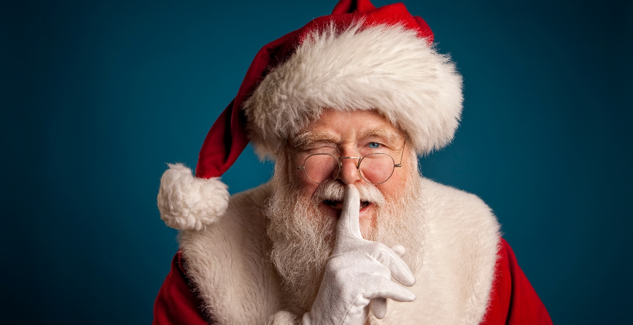 Father Christmas winking with a finger to his lips